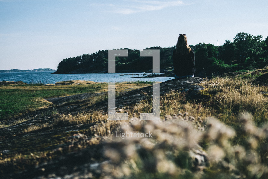a woman sitting on a shore looking out at the water Lysekil, Sweden