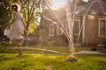 A little girl dances in the sprinklers in the warm golden light of summer.