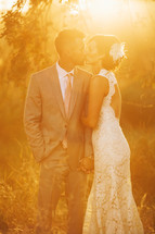 bride and groom kissing outdoors under the glow of the sun