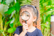 a toddler girl looking through a magnifying glass