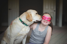 a child in a mask and her dog