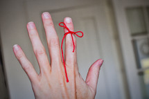 A red string is tied to a figure to remind the person of something.