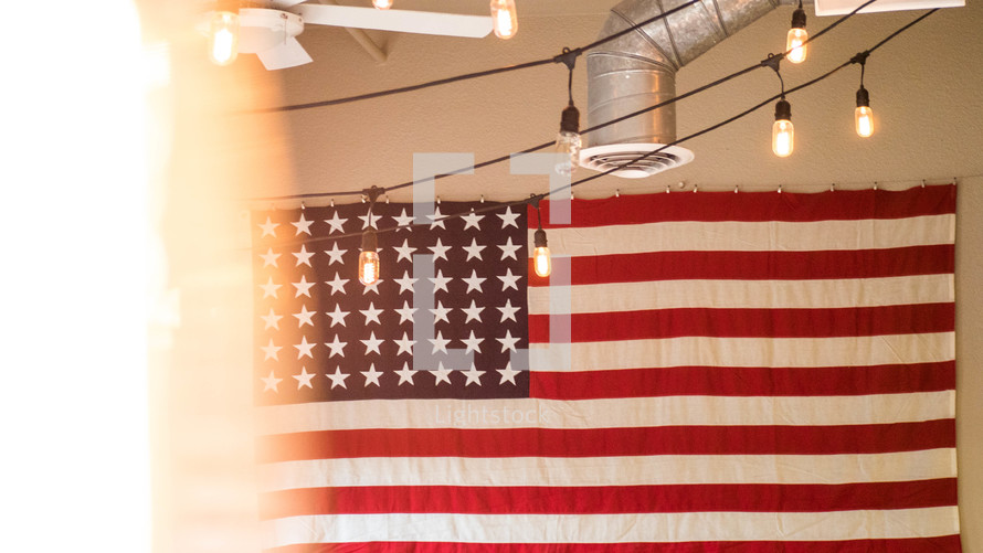 American flag hanging on a white and string of lights