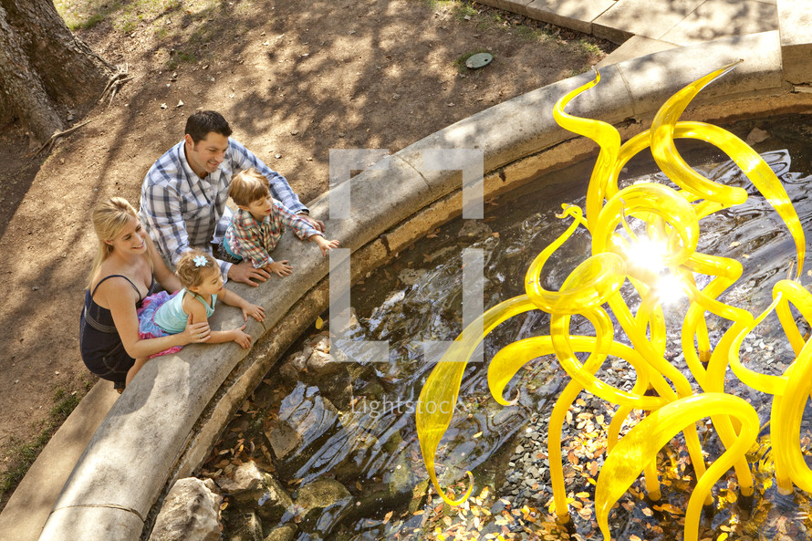 A young family by a water fountain
