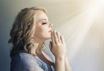 woman in prayer under heavenly light