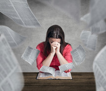 Woman praying while pages fly out of the Bible.