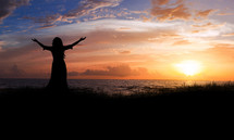 silhouette of a woman with arms raised in worship at sunset