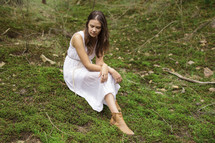 a young woman in dress siting on mossy ground