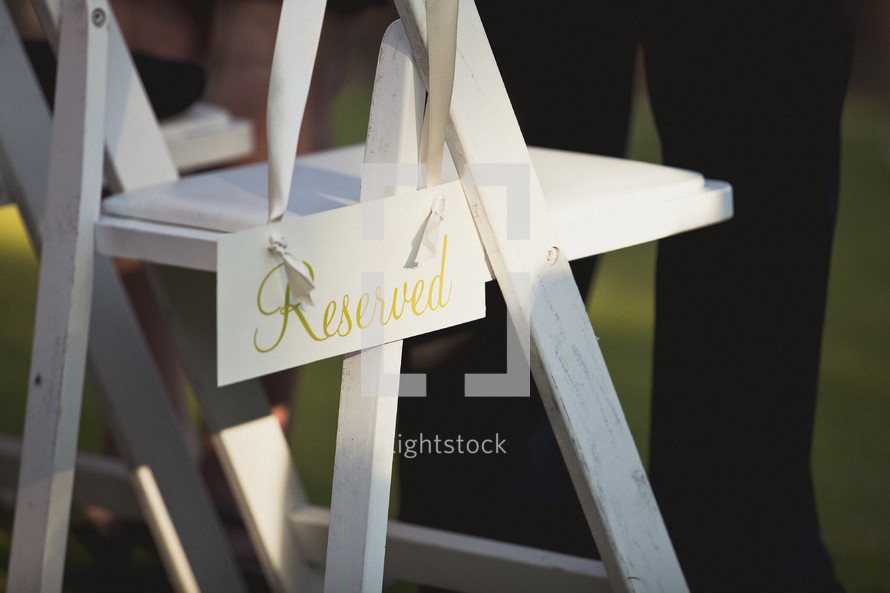 A reserved sign hanging on a white folding chair