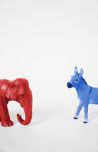 A red Republican elephant and a blue Democratic donkey facing off.