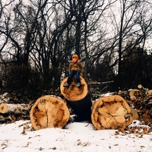 child on cut logs