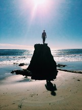 man on a rock at the beach