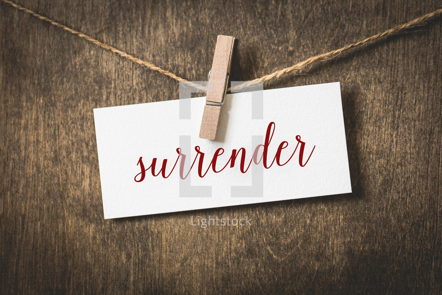 word surrender on white card stock hanging from a clothespin on a clothesline