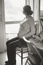 pregnant woman sitting holding her belly looking out a window