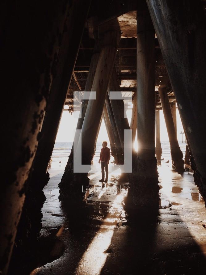 man standing under a pier