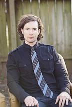 man wearing a tie sitting