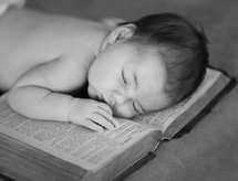 an infant sleeping on a Bible