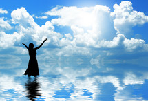 Silhouette of woman praising God in cloudy water.
