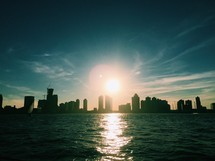 silhouettes of city skyscrapers across a bay at sunset in NYC