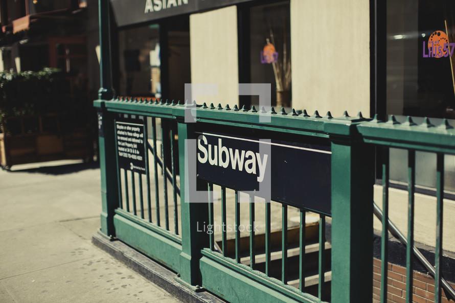 A Subway sign on a New York sidewalk