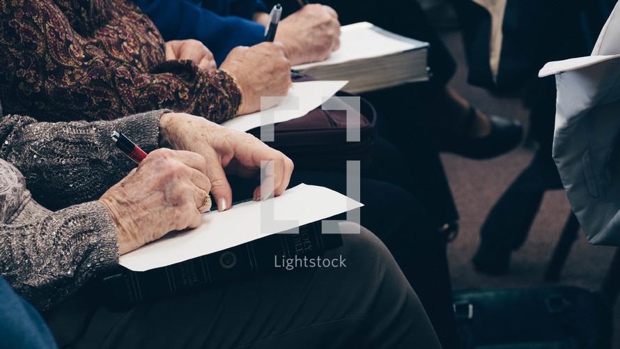elderly taking notes on Bibles