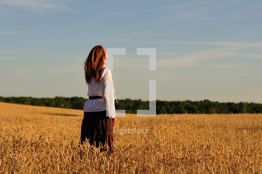 woman standing in a golden field of wheat