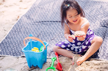 a little girl playing in the sand on a beach