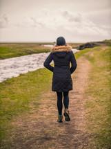 a woman walking on a path along a riverbank