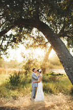groom kissing his bride on the forehead standing under a tree outdoors