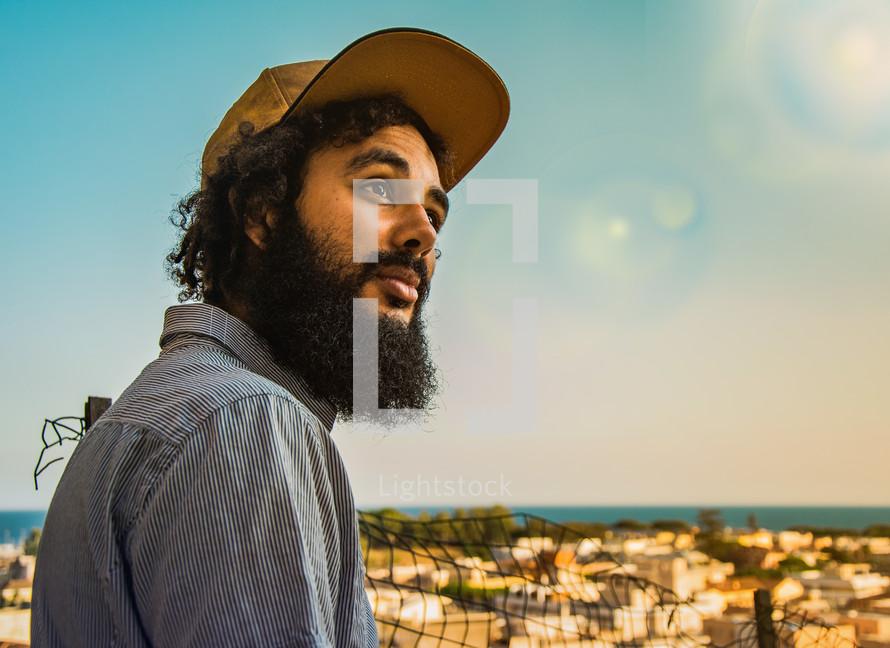 a man with a beard wearing a ball cap
