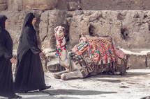 Arab women walking near a camel