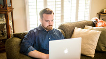 a man sitting on a couch typing on a laptop