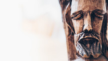 wooden carving of the face of Christ