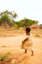 A small child walks barefoot in the dirt.