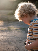 a blonde hair little boy playing outdoors