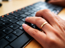 a woman's hand with wedding ring typing on a keyboard on a desk