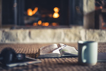 headphones, tablet, open Bible, pen, journal, and coffee cup by a fireplace