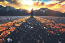 A man walking down a road towards a mountain sunset