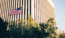 American flag on a flag pole and a tall building in the background