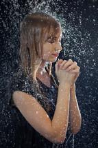 a woman praying under falling rain
