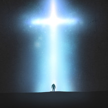 silhouette of a man standing under an illuminated cross