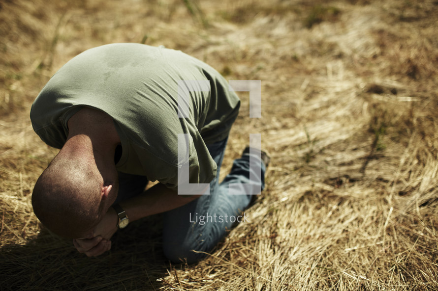A desperate man on his knees praying to God
