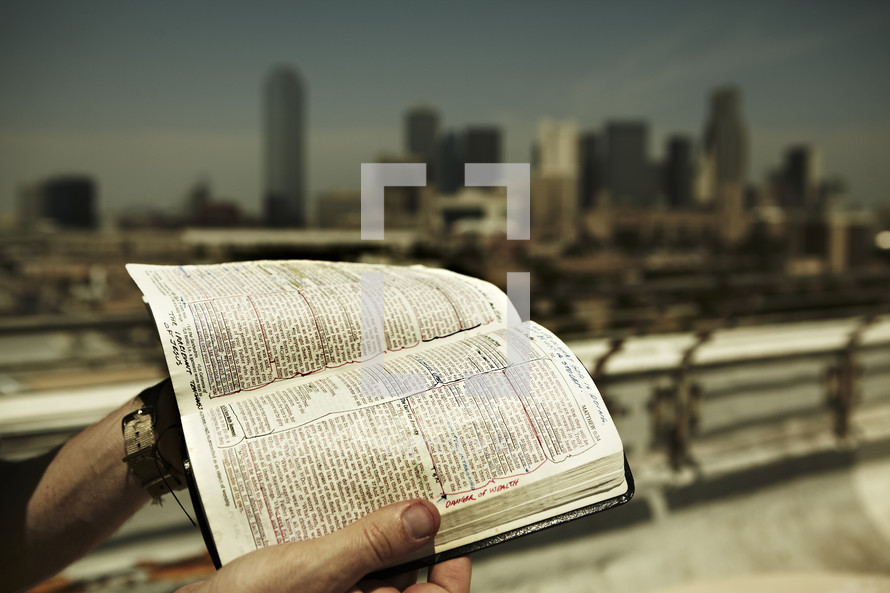 A man stands on the rooftop with an open Bible in hand overlooking the city of Dallas.