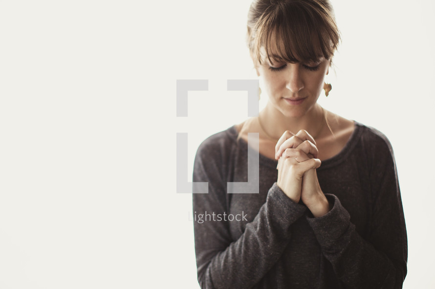 woman with her head bowed in prayer