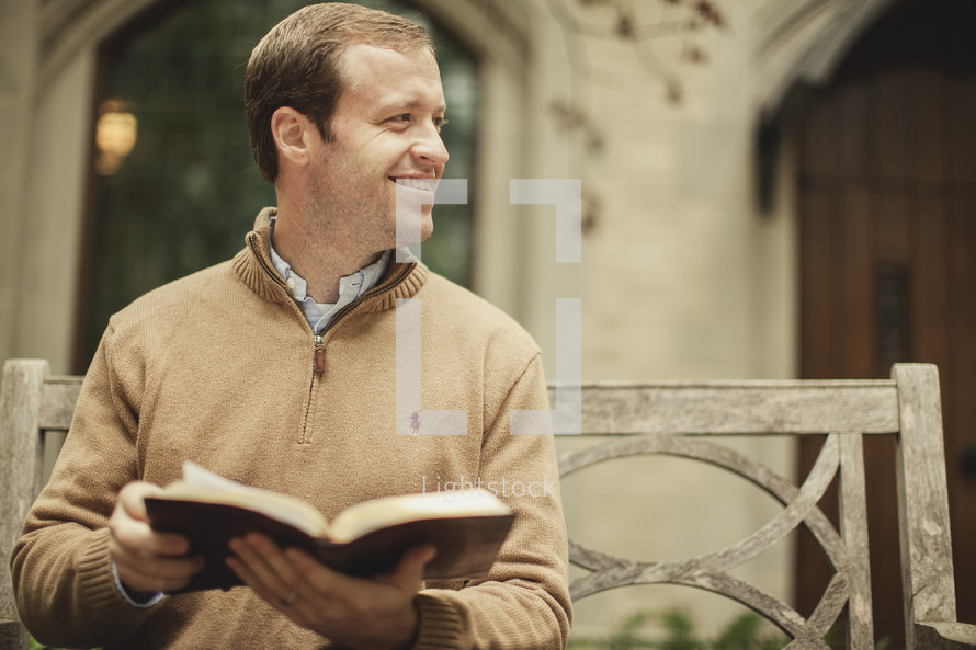 man sitting on a bench with an open Bible