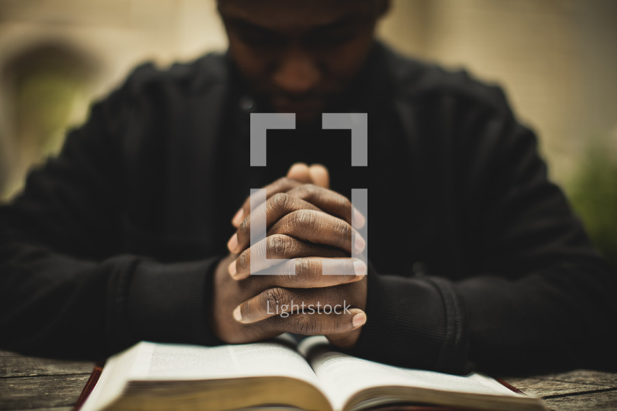 Man praying over Bible