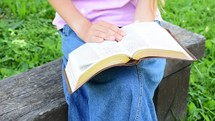 young lady sitting and reading a Bible