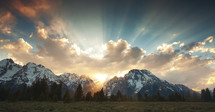 rays of sunlight behind snow capped mountains
