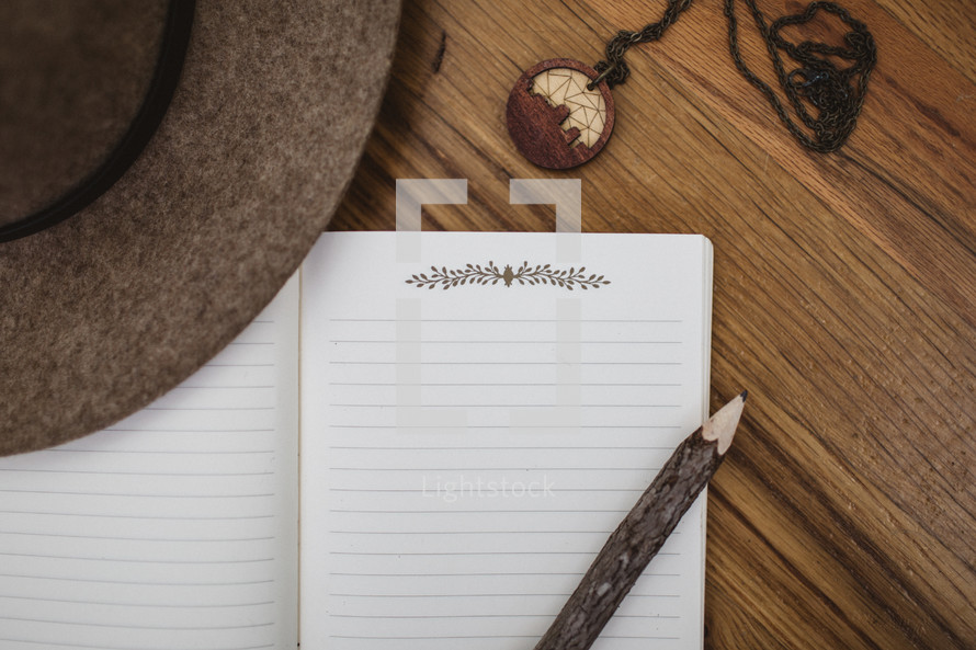 hat, necklace, pencil, and notebook on a wood floor