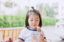a little girl eating a chocolate popsicle